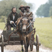 On a country road, Newt (Matthew McConaughey) drives the cart while Moses (Mahershala Ali) clutches onto his boy (La Jessie Smith)